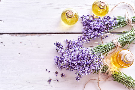 Lavender essential oils with bunches of fresh flowers tied with string on painted white wood boards with copy space in an overhead view