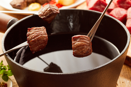 Fried portions of tender beef cooked in a fondue pot displayed on forks above the hot oil in a close up view