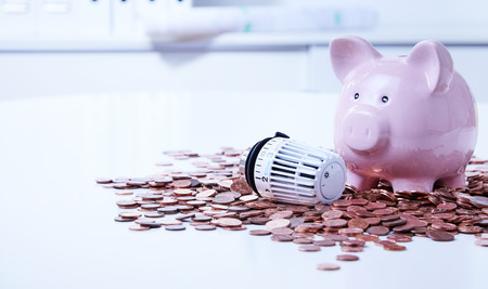 Thermostatic radiator valve with ceramic piggy bank among pile of saved coins Stock Photo