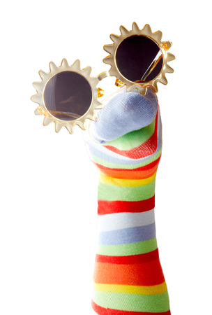 Funny colorful sock puppet with sunglasses isolated on white background Foto de archivo