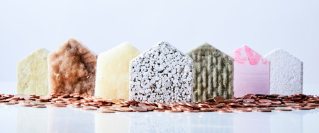 Seven house shapes made from various building materials in a triangle formation surrounded by coins. Stockfoto