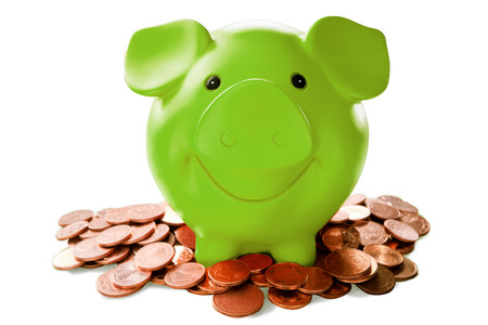 Green piggy bank among coins against white background
