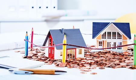 Deux maisons miniatures debout parmi les pièces de monnaie derrière la clôture construite de crayons de couleur Banque d'images - 82720020
