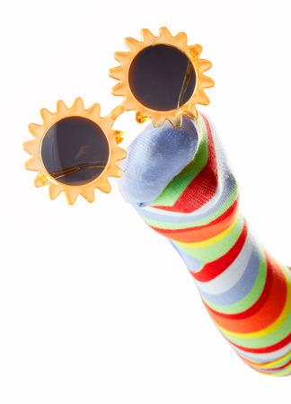 Gelukkige kleurrijke sokmarionet die zonnebril draagt ??die op witte achtergrond wordt geïsoleerd
