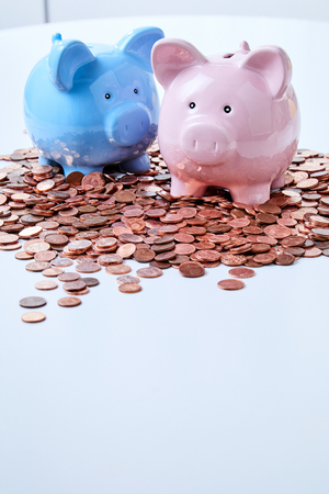 Two piggy banks standing among pile of coins