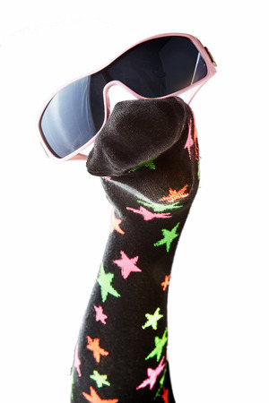 Fun woollen sock puppet with stars and sunglasses isolated on white in a close up view of the face for entertaining kids