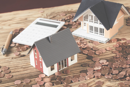 Two miniature houses, calculator, pen among saved coins on wooden table
