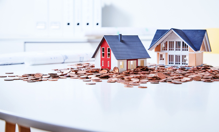 earned: Two miniature houses standing on table among heap of coins
