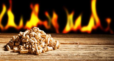 コピー スペース パノラマ ビューで自然な木質ペレットのヒープの背後に炎の燃焼の行の再生や持続可能なエネルギー コンセプト 写真素材