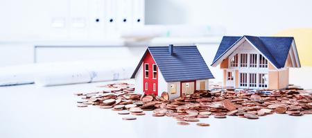 Two miniature houses among pile of coins Foto de archivo