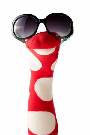 animate: Colorful red and white polka dot sock puppet wearing sunglasses for entertaining young kids isolated on white with copy space Stock Photo