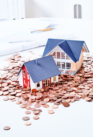 Two tiny miniatures of houses among pile of coins