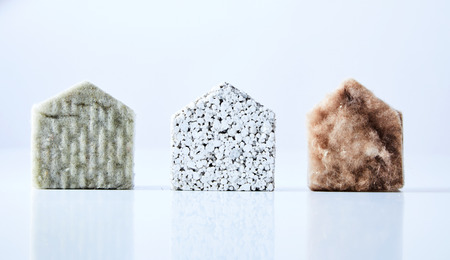Three natural coloured, textured house shapes made from building materials isolated on a white background.