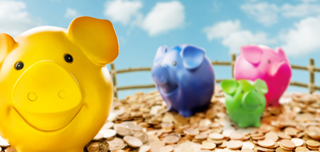 Four colourful piggy banks standing among coins against fencing and sky with clouds 版權商用圖片