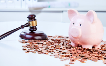 Piggy bank with wooden gavel among pile of coins 스톡 콘텐츠