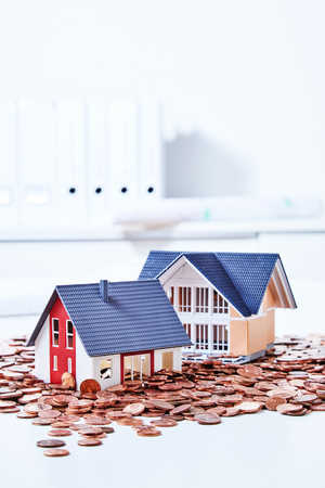 Two models of small houses among pile of coins Stock Photo