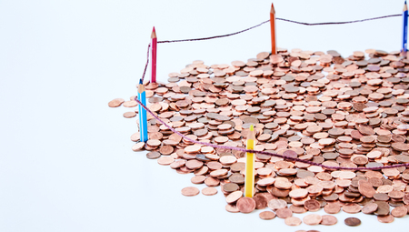 Pile of coins behind fencing built of colored pencils