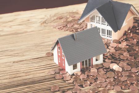Twee kleine modellen van huizen die zich op houten lijst onder muntstukken bevinden Stockfoto