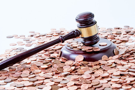 Wooden gavel and a pile of copper coins cropped closeup from high angle on white surface background, in concept of court corruption or successful auction sale deal