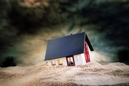 Klein model van huis gebouwd op stapel zand Stockfoto