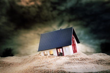 Small model of house built on pile of sand Reklamní fotografie - 82621846