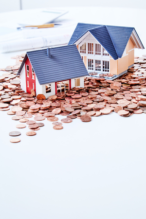 Miniatures of two houses standing among coins Stock Photo