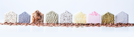 Nine textured house shapes surrounded by coins on an isolated white background representing an affluent residential street.