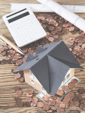 Cash, model hose, blue prints and calculator in a concept of financing the costs of a new home or improvements and renovations