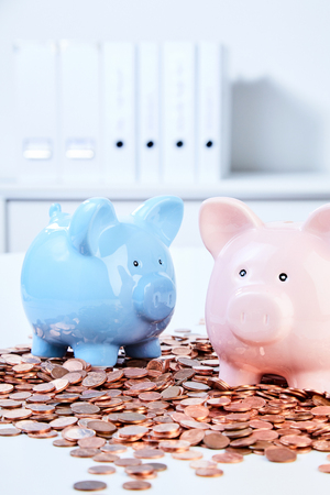 Two ceramic piggy banks standing on pile of coins 版權商用圖片 - 82621845