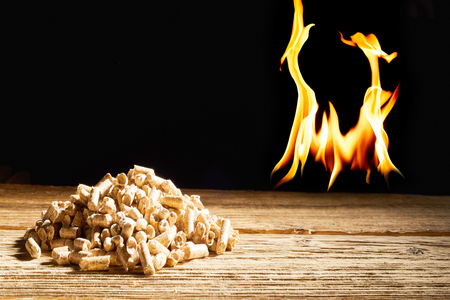 Flames burning in the darkness behind a heap of wood pellets on a rustic table in a concept of natural renewable fuel and energy with copy space