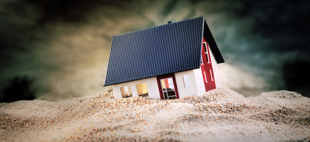 Miniature of house standing in pile of sand Stock Photo - 82621861