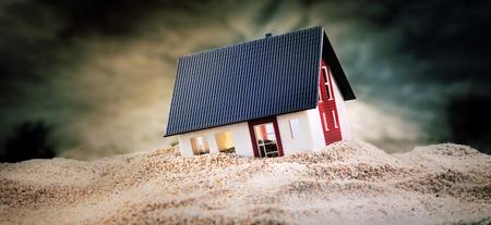 Miniatuur van huis staande in een stapel zand