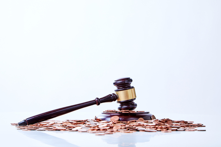 Wooden gavel on the pile of copper coins on glossy white surface and white background from the side with copy space
