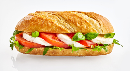 Baguette sandwich with Capresi salad filling of fresh tomatoes, lettuce and mozzarella cheese on a reflective white background Stock Photo