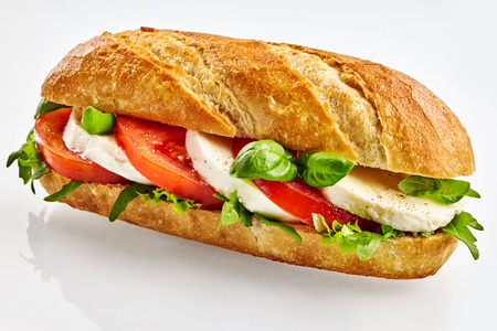 Fresh baguette sandwich with mozzarella cheese, tomato and basil