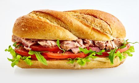 Ein frisches Salat Thunfischstangenbrotsandwich mit der Tomate, Kopfsalat und Fleisch lokalisiert auf einem weißen Hintergrund mit Kopienraum.