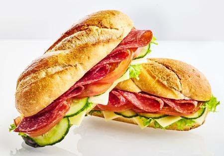 고기, 치즈, 오이 및 그린 샐러드와 함께 두 개의 신선한 버 게 트 빵 샌드위치
