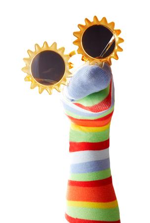 Grappige kleurrijke sokpopet met zonnebril geïsoleerd op een witte achtergrond Stockfoto