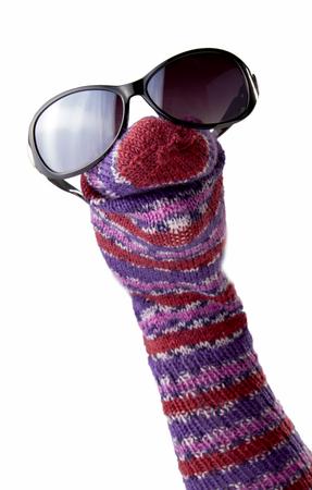 Marioneta de rayas de calcetines de colores con gafas de sol aisladas sobre fondo blanco Foto de archivo - 82861362