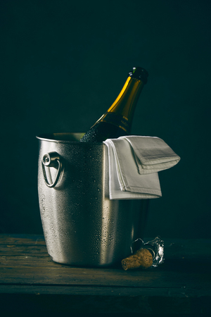 Open bottle of champagne waiting in metal bucket to be served Stock fotó