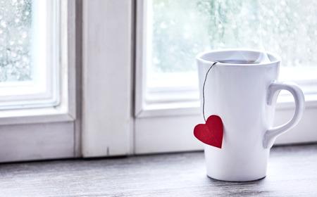 Ein dampfender heißer Becher Tee mit einem roten Liebesherztag auf einem Fensterbrett als helles Morgenlicht strömt durch.