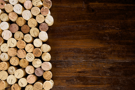 Rows of corks forming a side border on an old wooden background in a full frame view with copy space