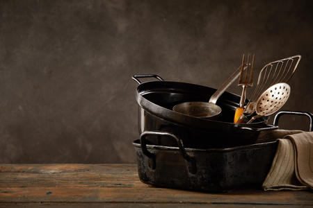 Set of kitchen pots and utensils standing on wooden countertop