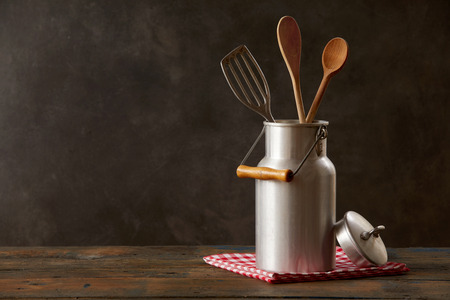 Still life of retro milk can with kitchenware standing on wooden table