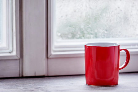 A red mug sitting on a kitchen window sill as bright morning light streams through from outside.
