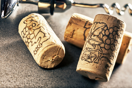 Close up of three wine corks and corkscrew in background