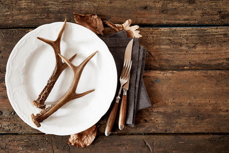 Deer antlers on plate with cutlery against wooden table Фото со стока
