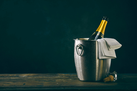 Bottle of champagne chilling in metal bucket