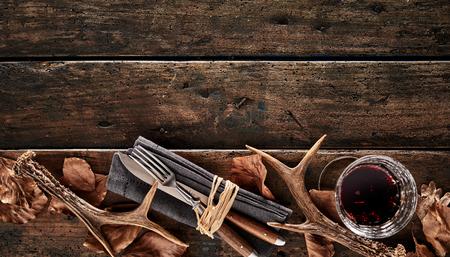 クワガタの角、茶色の紅葉、ナイフ、フォーク、素朴な木製の背景にウィスキーのグラス。