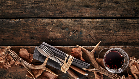 Stag antlers, brown autumn leaves, knife, fork and a glass of whiskey on a rustic wooden background. 版權商用圖片